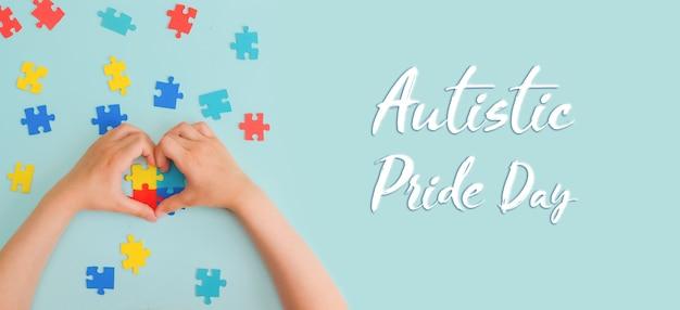 세계 자폐증 인식의 날 파란색 배경에 화려한 퍼즐을 들고 있는 어린 아이의 손