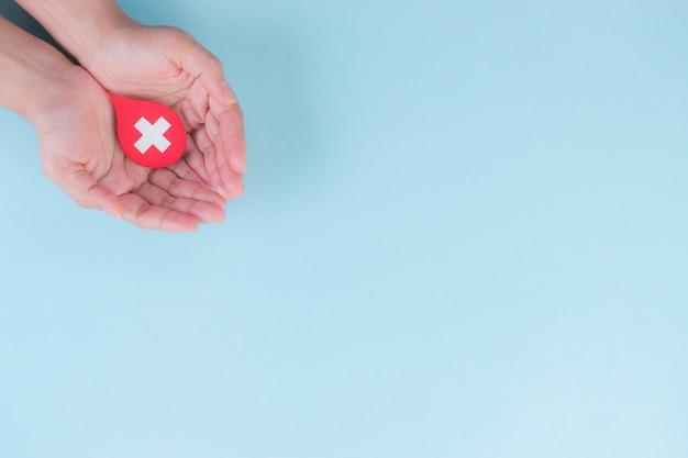 世界の献血者と血友病の日のコンセプトです。赤い血の滴を保持している女性の手。コピースペース。