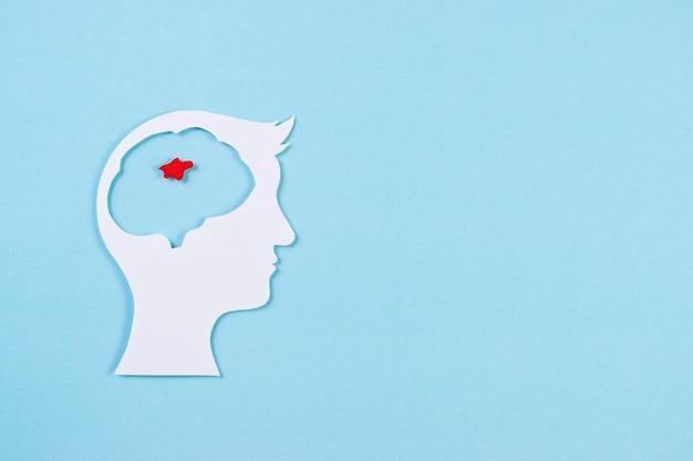 世界の脳腫瘍の日。明るい青の背景に赤い腫瘍のカット紙の脳の平面図。コピースペース
