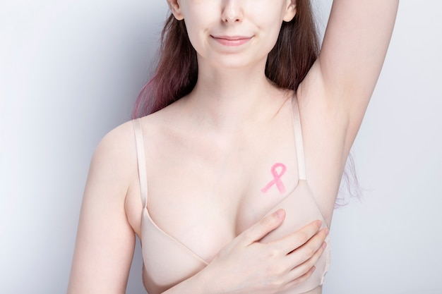 World breast cancer day concept. woman in bra with pink ribbon painted on her chest. october breast cancer awareness month