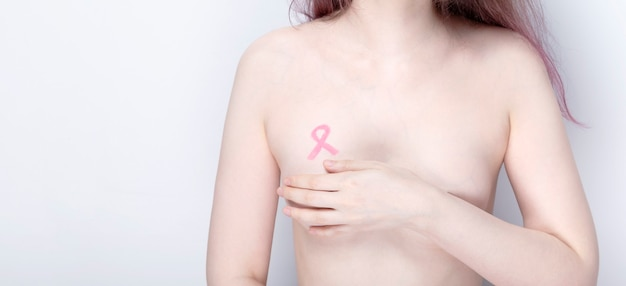 World breast cancer day concept. woman covers her chest with her hands with painted pink ribbon. october breast cancer awareness month.