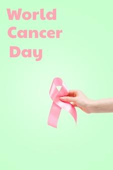 Всемирный день борьбы с раком. женская рука с розовой лентой на светло-зеленом фоне. вертикальная ориентация. скопируйте пространство.