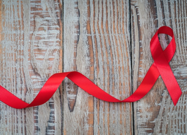 World cancer day : breast cancer awareness ribbon on wood backgr