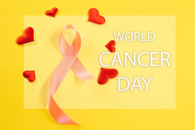 World cancer day card with pink ribbon and red hearts