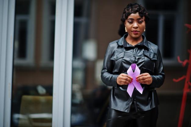 Концепция всемирного дня борьбы с раком, 4 февраля. афро-американская женщина держит фиолетовую ленту осведомленности.