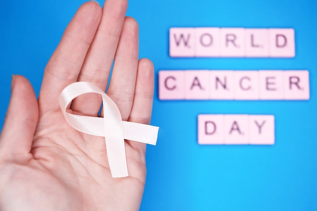 World cancer day, february 4th. woman holds pink ribbon on hand