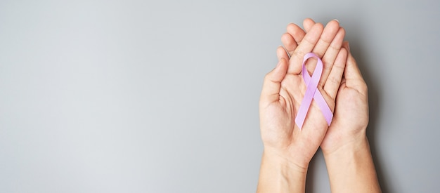 World cancer day. woman hand with pink ribbon for supporting people living and illness.
