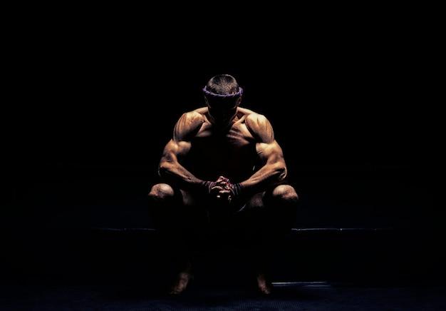 タイボクシングの世界チャンピオンはリングに座って、次の戦いの準備をしています。スポーツ、健康的なライフスタイル、スポーツ栄養の概念。ミクストメディア