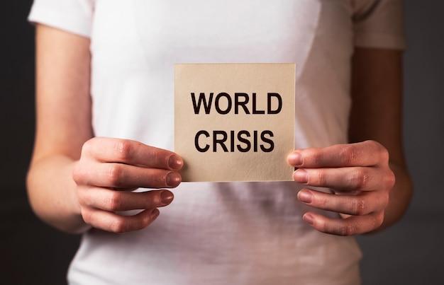 女性の手の紙に世界危機の碑文。