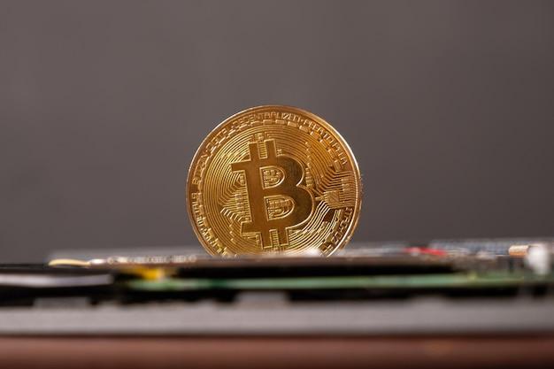 Мировая криптовалюта, золотая монета биткойн крупным планом.