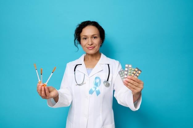세계 당뇨병의 날. 11월 14일. 파란색 인식 리본을 두른 흰색 의료 가운을 입은 아름다운 여성 의사는 인슐린 주사기와 약품 정제를 물집에 들고 카메라를 바라보며 미소를 짓고 있습니다.
