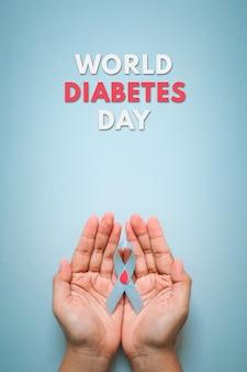 파란색 배경에 격리된 여성의 손에 붉은 피가 떨어지는 세계 당뇨병의 날과 파란색 리본 인식. 11월 14일 세계 당뇨병의 날. 공간을 복사합니다. 평면도