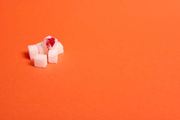 World diabetes day awareness concept, 14 november. pure refined white sugar cubes with blood drop, isolated over colored orange background with copy space for medical advertising