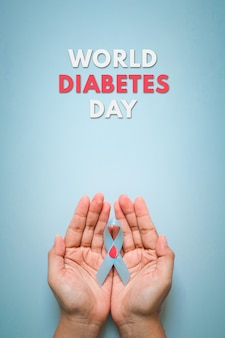 World diabetes day and blue ribbon awareness with red blood drop in woman hands isolated on a blue background. world diabetes day,14 november. copy space. top view