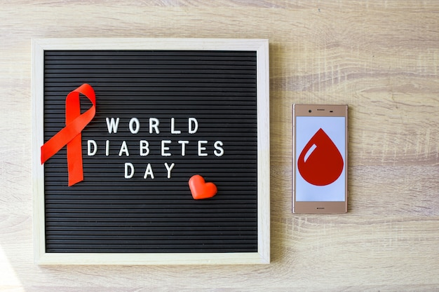 World diabetes day creative flat lay concept with red ribbon blood symbol drugs and syringe