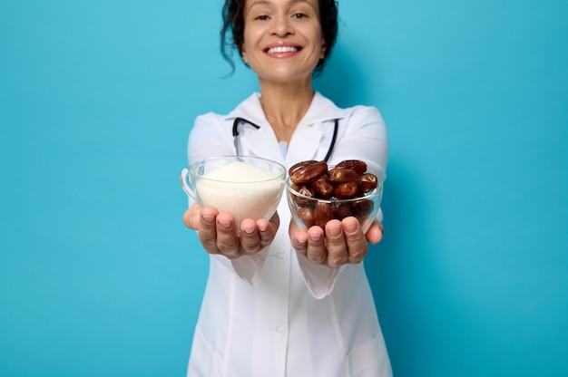 Всемирный день диабета. сосредоточьтесь на прозрачных стеклянных мисках со спелыми сладкими финиками и нездоровым белым рафинированным сахаром в руках диетолога-врача, изолированного на синем фоне с копией пространства.