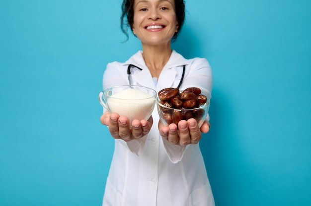 World diabetes day. focus on transparent glass bowls with ripe sweet dates and unhealthy white refined sugar on the hands of female doctor nutritionist, isolated over blue background with copy space.