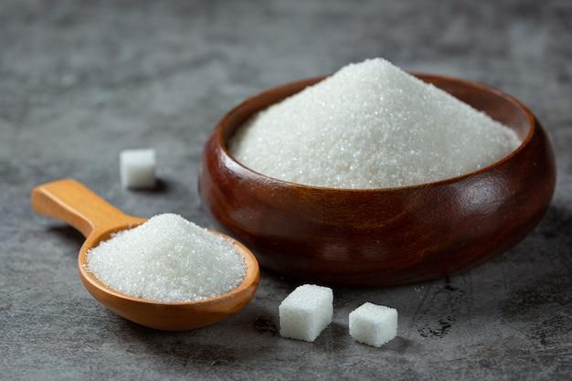 Giornata mondiale del diabete; zucchero in una ciotola di legno sulla superficie scura