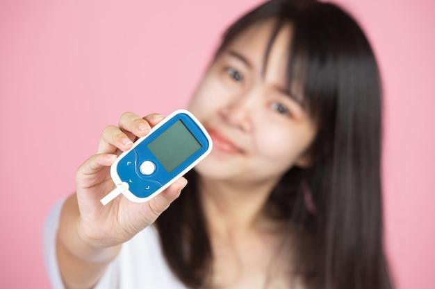 Giornata mondiale del diabete; donna che tiene misuratore di glucosio sulla parete rosa
