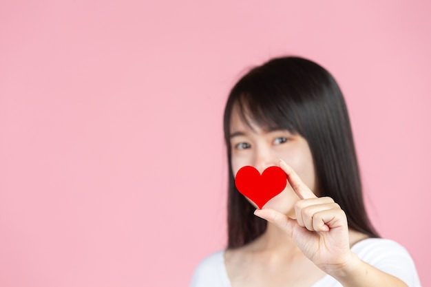 Всемирный день борьбы с диабетом; женщина держит красное сердце на розовой стене