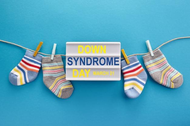 世界ダウン症の日の背景。ダウン症の意識の概念。青い背景の靴下とライトボックス