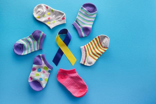 世界ダウン症の日の背景。ダウン症の意識の概念。青い背景の上の靴下とリボン