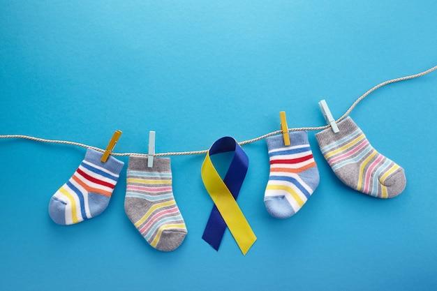 세계 다운 증후군의 날 배경. 다운 증후군 인식 개념. 양말과 파란색 배경에 리본