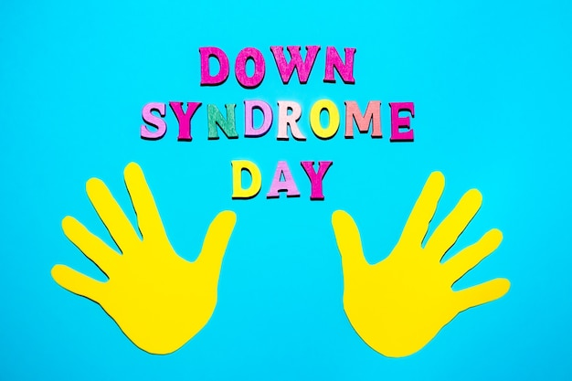 World down syndrome day - inscription laid out of wooden letters on blue background and yellow baby palms. down syndrome awareness concept. banner, illustration, poster.