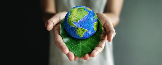 Концепция всемирного дня земли. зеленая энергия, возобновляемые и устойчивые ресурсы. забота об окружающей среде и экологии. рука обнимает зеленый лист и глобус ручной работы