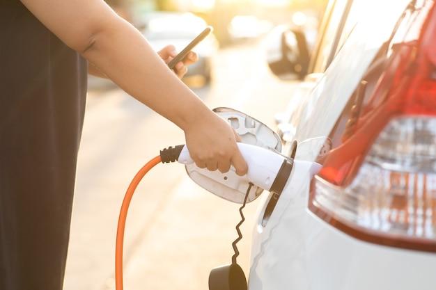 Всемирный день окружающей среды. крупным планом женская рука с вилкой электромобиля для подзарядки