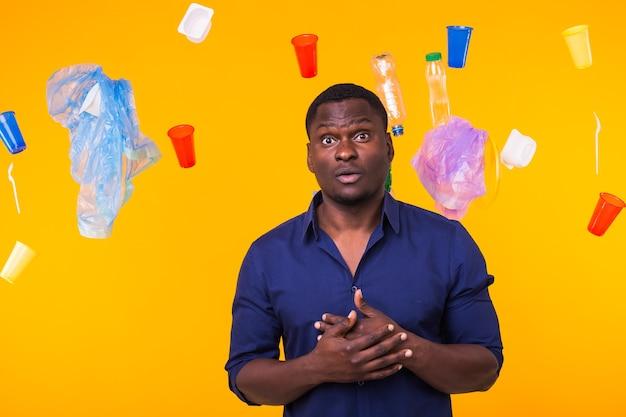世界環境デー、プラスチックのリサイクル問題と環境災害の概念-ゴミのある黄色い壁の恐怖の男。