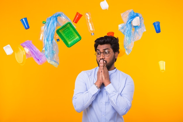 World environment day, plastic recycling problem and environmental disaster concept - scared indian man is standing under trash and looking side on yellow background