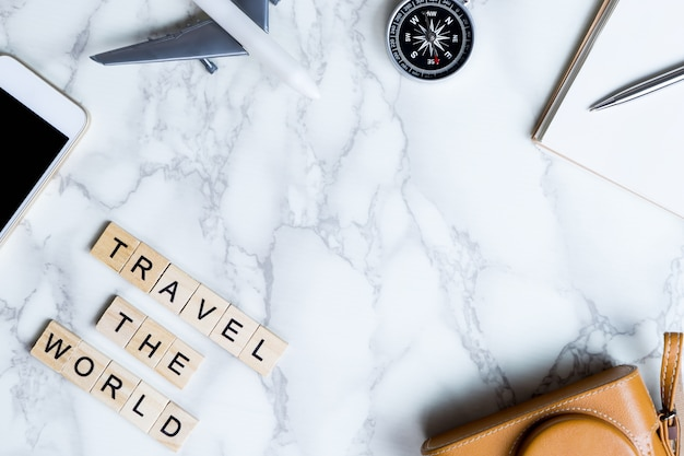 World explorer blogger accessories on luxury white marble table with copy space in middle