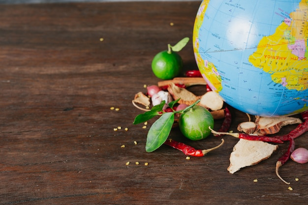 The world food day, a car-packed spice and fresh colors placed on a simulated globe on a brown wooden floor.