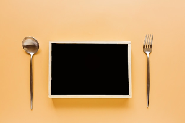 World food day concept with black chalkboard and cutlery