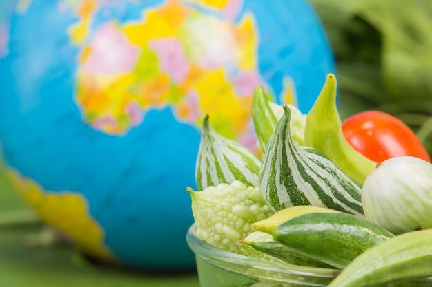 世界の食べ物の日、多くの野菜は緑のバナナの葉の近くに置かれた地球儀とボウルにあります。