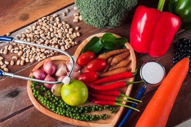 Всемирный день еды, различные свежие органические фрукты и овощи в сердечной пластине и медицинском стетоскопе