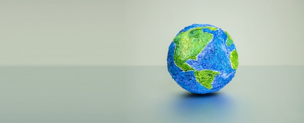 World, global, earth day concept. handmade globe against light grey wall. clean and minimal composition. wide space for text