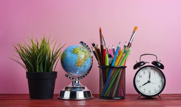 World globe, alarm clock, plant and school stationary in basket on wooden table pink background