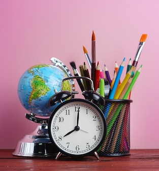 World globe, alarm clock, and school stationary in basket on wooden table pink background