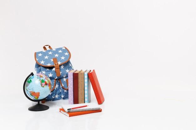 世界の地球儀、星のプリントとカラフルな教科書が分離された青いバックパック。学生のためのアクセサリー、消耗品。高校大学の概念における教育