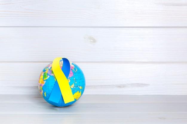 木製の背景に黄色と青のリボンと世界の地球。世界ダウン症の日のコンセプト。テキスト用のスペース。