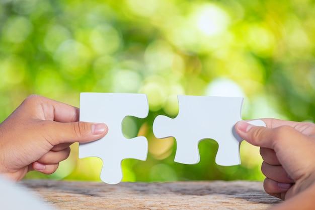 Всемирный день среды обитания, крупным планом кусок белой головоломки в каждой руке
