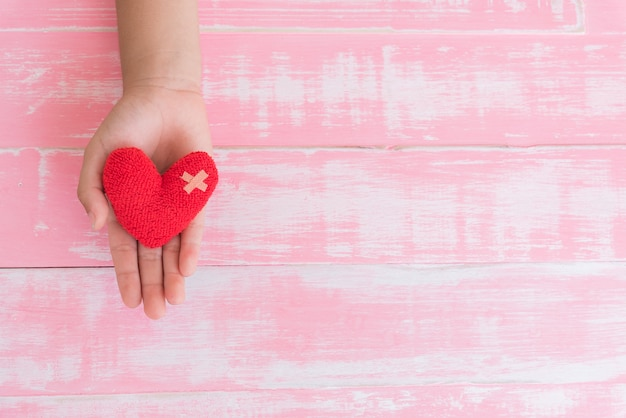 World health day, child hand holding handmade red heart on pink wooden background