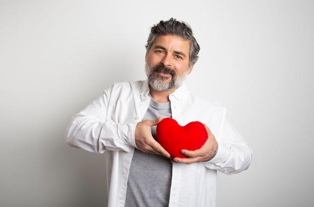 세계 심장의 날 흰색 배경 붉은 마음을 잡고하는 남자. 행복한 발렌타인 데이