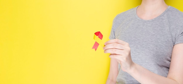World hepatitis day concept. girl in gray t-shirt holds in her hand awareness symbol red-yellow ribbon. yellow background. copy space