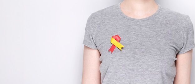 World hepatitis day concept. girl in gray t-shirt with pinned awareness symbol red-yellow ribbon. gray background. copy space