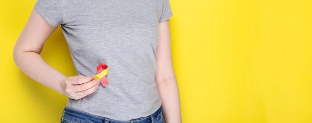 Концепция всемирного дня борьбы с гепатитом. девушка держит красно-желтую ленту в районе liveras символ осведомленности