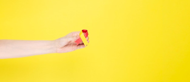 World hepatitis day concept. woman holds in her hand awareness symbol red-yellow ribbon. yellow background. copy space