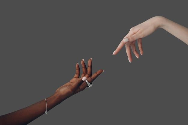 Всемирный день гуманитарной помощи. кавказские белые и афро-американские черные руки протягивают друг другу руки на сером фоне.